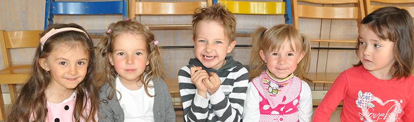 Fünf Kleinkinder sitzen in einer Reihe