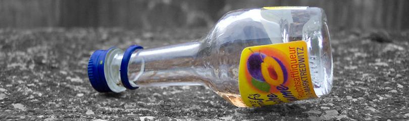 Leere Glasflasche liegt auf dem Boden