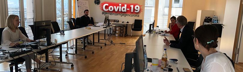 Die Mitglieder des Lagezentrums Corona sitzen in einem großen Besprechungsraum