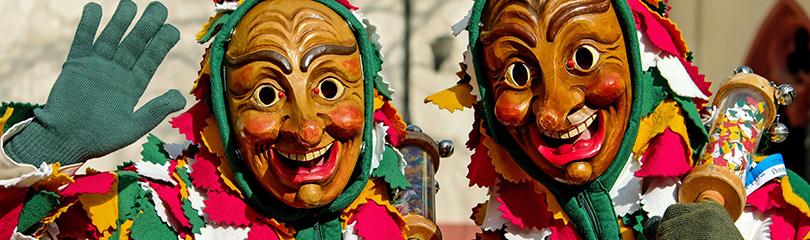 Narren in Kostümen mit Holzmasken
