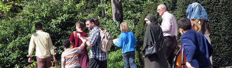 Personen unterschiedlicher Herkunft spazieren auf einem Weg im Park