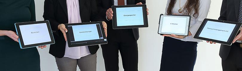 Fünf Personen zeigen kleine Bildschirme