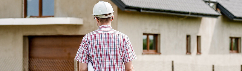 Ein Mann mit Helm steht vor einem Haus, welches gebaut wird.