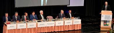 Bühne mit Sitzplätzen für Gäste, darunter Winfried Kretschmann, und Sprecherpult an dem Gemeindetagspräsident Kehle spricht