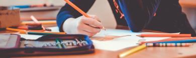 Kind mit Stift in der Hand malt auf Papier.